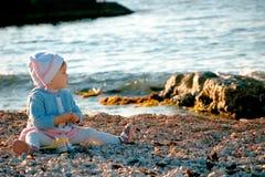 Um bebê que senta-se perto do mar Foto de Stock Royalty Free