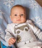 Um bebê que veste um bodysuit com uma coruja que encontra-se em uma cobertura azul com flocos de neve imprime fotografia de stock royalty free