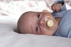 Um bebê recém-nascido pequeno suga uma chupeta A criança é feita crochê fotos de stock royalty free