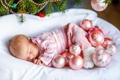 Um bebê recém-nascido semanas de idade com bolas cor-de-rosa aproxima a árvore de Natal Foto de Stock Royalty Free