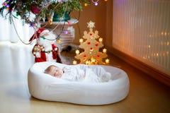 Um bebê recém-nascido semanas de idade que dorme perto da árvore de Natal Fotos de Stock Royalty Free
