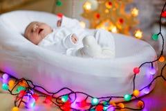 Um bebê recém-nascido semanas de idade que dorme perto da árvore de Natal Imagem de Stock