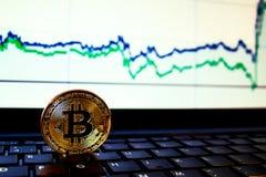 Um bitcoin dourado com fundo do teclado e do gráfico conceito de troca da moeda cripto Imagens de Stock