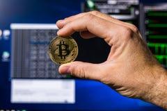 Um bitcoin dourado em uma mão do ` s da mulher em um fundo brilhante do close-up dos gráficos de negócio moeda Bitcoin-cripto foto de stock royalty free