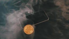 Um Bitcoin físico em uma tela do ` s do smartphone no fundo preto video estoque