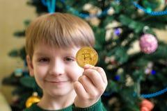 Um Bitcoin na mão do menino novo Conceito Ouro digital cripto foto de stock royalty free
