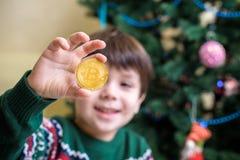 Um Bitcoin na mão do menino novo Conceito Ouro digital cripto imagem de stock