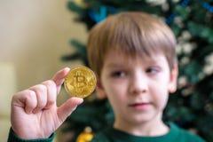 Um Bitcoin na mão do menino novo Conceito Ouro digital cripto fotografia de stock