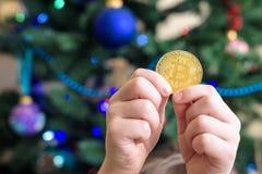 Um Bitcoin na mão do menino novo Conceito Ouro digital cripto fotografia de stock royalty free