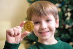 Um Bitcoin na mão do menino novo Conceito Ouro digital cripto fotos de stock royalty free