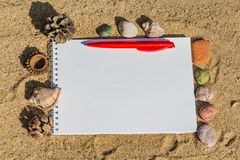 Um bloco de notas branco com uma mola branca com mentiras vermelhas de uma pena de esferográfica em uma superfície amarela da are imagem de stock