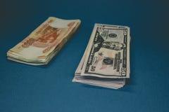 um bloco de rublos e de d?lares de russo dois punhados do dinheiro em um fundo azul riqueza da oportunidade Sucesso foto de stock