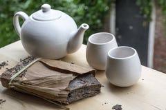 Um bloco do chá preto com teakettle branco e dois copos fotografia de stock