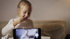 Um blogger novo, engraçado da menina faz um registro da edição A criança desembala o ovo com uma surpresa video estoque