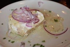 Um bocado do queijo do camembert conservado no óleo com anéis de cebola em uma placa branca fotografia de stock royalty free