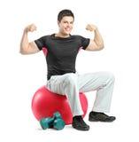 Um bodybuilder novo que senta-se em uma esfera dos pilates Imagens de Stock Royalty Free