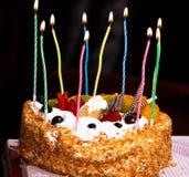 Um bolo de aniversário iluminado com velas foto de stock