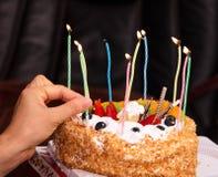 Um bolo de aniversário iluminado com velas imagens de stock