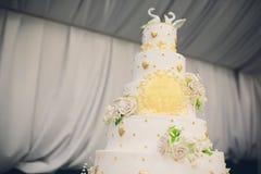 Um bolo de casamento branco alto decorado com flores do ouro e as cisnes brancas Duas partes são eliminadas imagem de stock royalty free