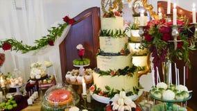 Um bolo de casamento tradicional e decorativo no copo de água video estoque