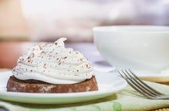 Um bolo de chocolate com creme da clara de ovos, um copo do chá quente e uma forquilha em uma tabela de madeira imagem de stock