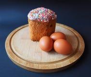 Um bolo de easter com os ovos na placa de madeira foto de stock