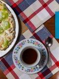 Um bolo feito dos biscoitos, decorados com fatias do quivi, mentiras em uma placa branca ao lado de uns pires e um copo do chá pr imagens de stock royalty free