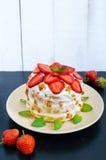 Um bolo festivo com morangos frescas, creme, decorado com folhas de hortelã Fotografia de Stock