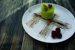 Um bolo pequeno do pistache com um revestimento verde e decorado com viburnum, molho dos confeitos em um fundo preto Vista latera foto de stock royalty free
