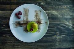 Um bolo pequeno do pistache com um revestimento verde e decorado com viburnum, molho dos confeitos em um fundo preto Vista latera fotografia de stock