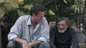 Um bom relacionamento com seu pai O homem branco-de cabelo e um homem novo que ri e que abraça 4K filme