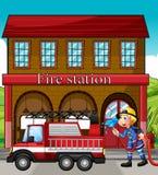 Um bombeiro e um carro de bombeiros na frente do quartel dos bombeiros Foto de Stock Royalty Free