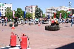 Um bombeiro em um terno à prova de fogo corre e gerencie um grande de borracha roda dentro uma competição da luta contra o incênd foto de stock