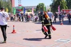 Um bombeiro em um terno à prova de fogo e um capacete extinguem um fogo em uma competição de esporte do fogo, Bielorrússia, Minsk fotografia de stock