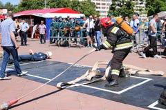 Um bombeiro em um terno à prova de fogo e em um capacete que guardam uma mangueira de fogo em uma competição de esporte do fogo M fotografia de stock