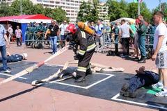 Um bombeiro em um terno à prova de fogo e em um capacete que guardam uma mangueira de fogo em uma competição de esporte do fogo M imagem de stock royalty free