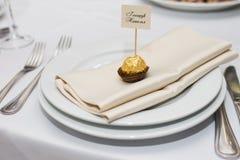 Um bonbonniere do casamento com lugar do nome nele que encontra-se em uma placa branca Fotografia de Stock Royalty Free