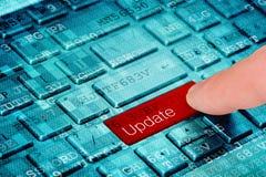 Um botão vermelho da atualização da imprensa do dedo no teclado digital azul do portátil imagem de stock