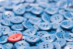 Um botão vermelho em um montão de botões azuis saiu baseado Foto de Stock
