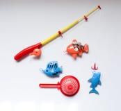 Um brinquedo ajustou-se pescando com uma vara de pesca e um peixe Fotos de Stock