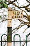 Um britânico velho um suporte de táxi solitário isolado e orlado no cerco da floresta e do ferro forjado Sinais das épocas idas p imagens de stock