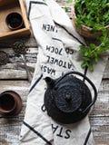 Um bule preto com chá verde e um copo para o chá ao lado de um ramo da hortelã Imagem de Stock Royalty Free