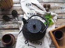 Um bule preto com chá verde e um copo para o chá ao lado de um ramo da hortelã Imagem de Stock