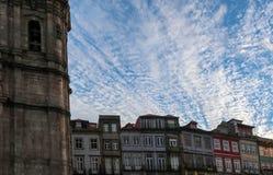 Um céu azul brilhante com as nuvens brancas acima dos telhados das casas fotografia de stock royalty free