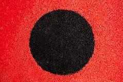 Um círculo preto em um fundo vermelho imagens de stock royalty free