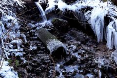 Um córrego congelado no inverno Ribeiro congelado com sincelo em uma caverna imagem de stock royalty free