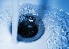 Um córrego da água derrama no dissipador na luz azul, higiene do banheiro foto de stock royalty free