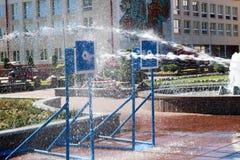 Um córrego molhado, poderoso da água espirra e tiros no alvo, com muita pressão na rua na atração fotos de stock