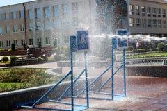 Um córrego molhado, poderoso da água espirra e tiros no alvo, com muita pressão na rua na atração foto de stock royalty free