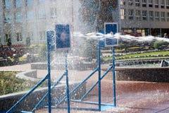 Um córrego molhado, poderoso da água espirra e tiros no alvo, com muita pressão na rua na atração imagem de stock